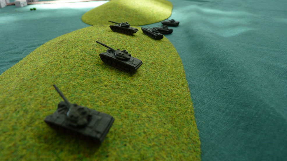 A platoon of T72s takes up position behind the crest